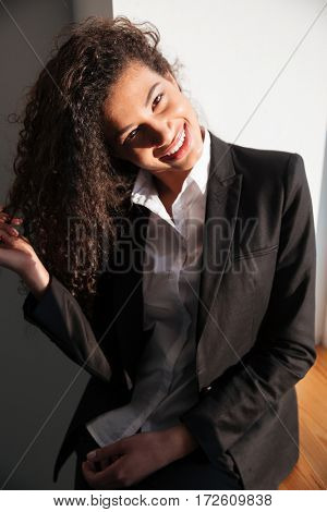 Photo of gorgeous african businesswoman standing over white background near window. Looking at camera.