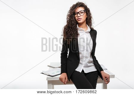 Image of incredible african business lady wearing glasses standing near table over white background. Looking at camera.