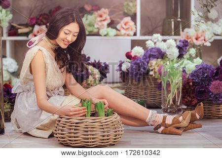 Beautiful girl in tender white dress sitting on the floor against floral background in flower shop. Joyful asian female florist. Playful fashion model looking and touching many spring flowers and smiling.