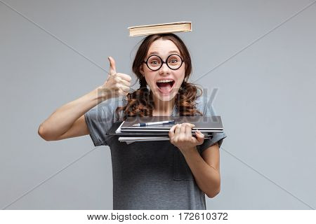 Happy Female nerd in funny eyeglasses with book on head which holding laptop and notebook in hand and showing thumb up