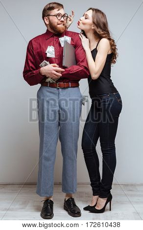 Vertical image of Pretty Woman stick to Male nerd with money. Isolated gray background