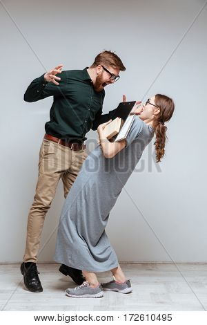 Vertical image of Bearded man screaming on the wronged female nerd