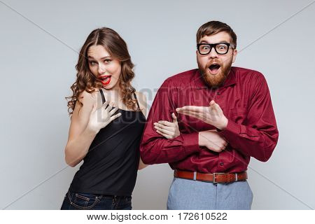 Funny Woman which holding hand of Shocked Male nerd in funny clothes and eyeglasses