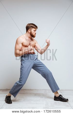 Side view of Male nerd as fighter with naked torso