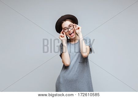 Happy Female nerd in black hat which holding for her eyeglasses