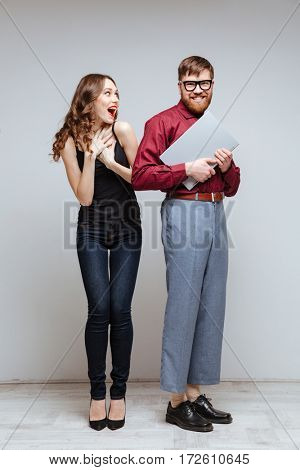 Vertical image of Happy Surprised woman with Male nerd in eyeglasses and funny clothes which holding laptop