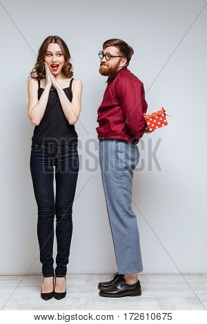 Vertical image of Male nerd presents the gift for Happy Woman. Isolated gray background