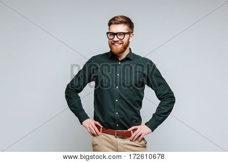 Smiling Bearded man in shirt and eyeglasses which posing with arms at hip