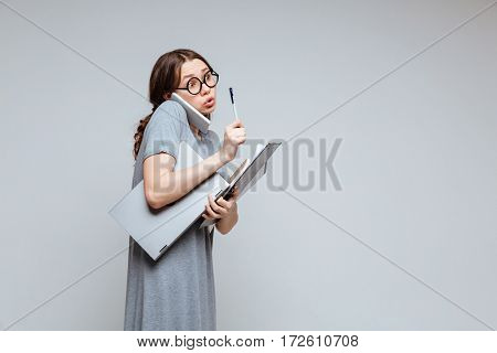 Young female nerd talking on phone and having idea