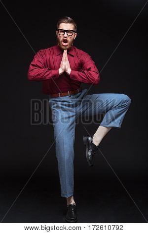 Vertical image of Male fighter nerd in eyeglasses posing in studio. Isolated black background