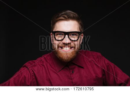 Smiling Bearded Male nerd in funny eyeglasses looking at camera. Isolated black background