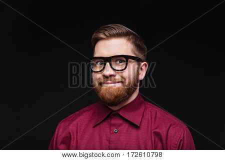 Smiling Male nerd in funny eyeglasses looking at camera. Isolated black background