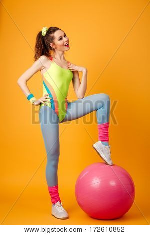 Photo of attractive young fitness lady posing over yellow background. Looking at camera.