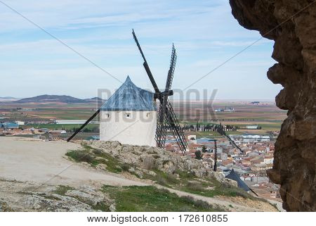 White old windmills on the hill near Consuegra (Castilla La Mancha Spain) a symbol of region and journeys of Don Quixote (Alonso Quijano) and a town on cloudy day.