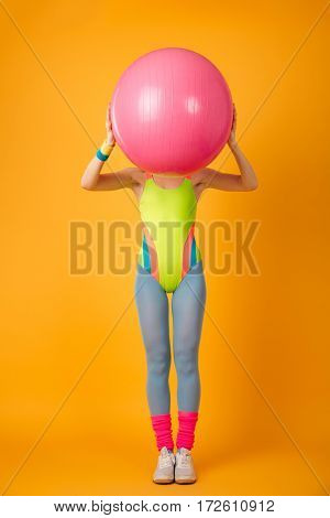 Picture of attractive young sports woman posing over yellow background with fitness ball.