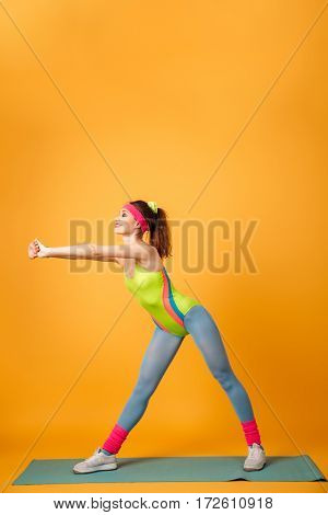 Picture of amazing young sports lady make sports exercises over yellow background. Looking aside.