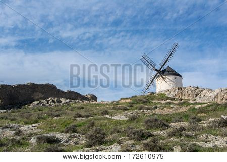 White old windmill on the hill near Consuegra (Castilla La Mancha Spain) a symbol of region and journeys of Don Quixote (Alonso Quijano) on cloudy day.