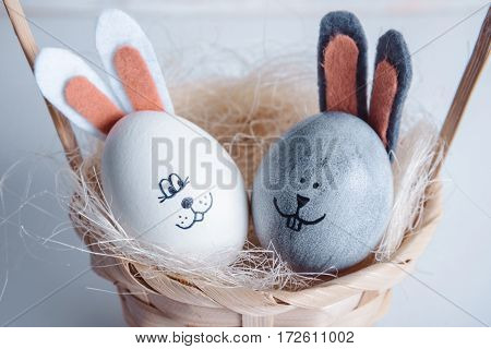 Cute creative eggs looks like bunny on white wooden background