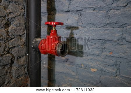Red tap on the pipe on the brick wall background.