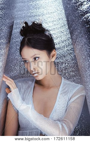 Portrait of futuristic young woman. Beautiful young multi-racial asian caucasian model cyber girl in silver urban clothes with conceptual hairstyle and make-up in metallik silver capsule. Sci-fi poster style.