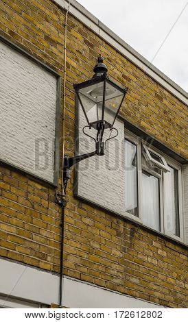 street lamp stylized at the old gas lamp the lamp placed on the facade of the building between the two windows residential building with bricks interesting decoration