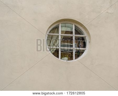 Interestingly round window in the wall of the building the window glass is reflected brick building across the street creamy wall and white window