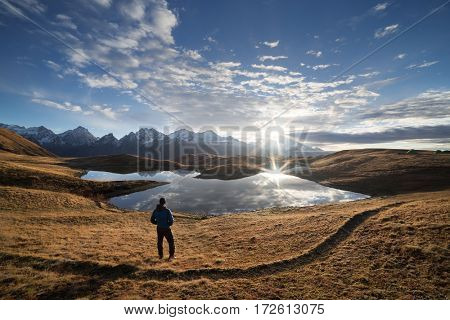 Landscape with mountain lake. Man tourist is standing on a slope and looks at the rising sun. Beautiful clouds reflected in water. Main Caucasian ridge. Koruldi lake, Zemo Svaneti, Georgia.