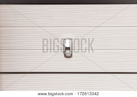A white desk drawer with a metal handle in the middle