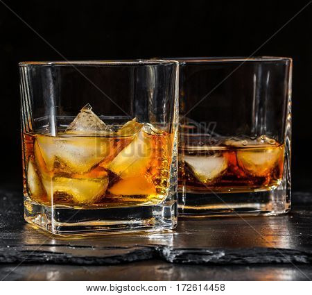 two glass of whisky with ice on a black background