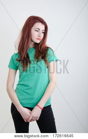 Young woman on a white background in a green shirt