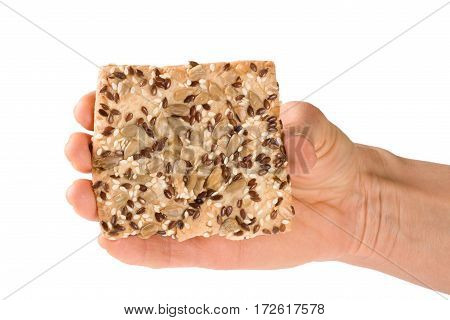 crispy bread with seeds of sunflower, flax and sesame seeds in hand Isolated on white background.