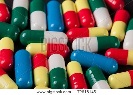 a lot of colorful pills on a dark background