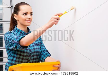 Woman painting the wall in DIY concept