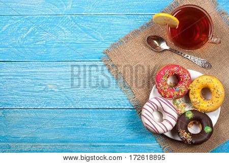 glazed donuts with a cup of tea on a blue wooden background with copy space for your text. Top view.