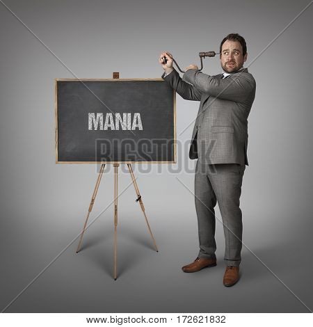 Mania text on blackboard with businessman drilling his head