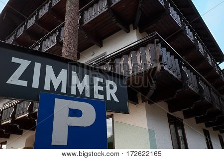 Sign Zimmer with chalet background in Alps