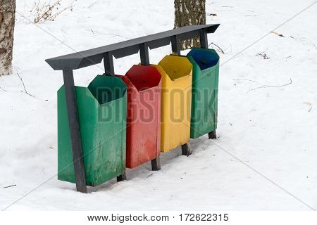 Colorful Trash Bins In The Snow In Winter Park.