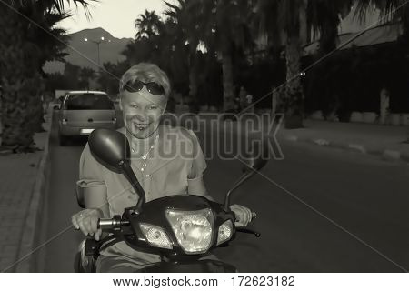 Woman mature smiling behind the wheel scooter. Black and white retro photo