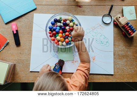 Overhead view of a toddler boy picking a bead out of a bowl