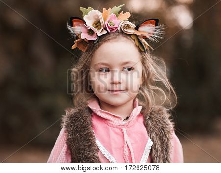 Smiling kid girl 3-4 year old wearing hairband with felt flowers outdoors. Summer portrait. Childhood.