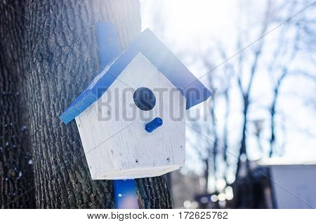Wooden birdhouse hanging on a tree background