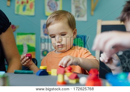 Focused toddler playing with blocks and learning shapes