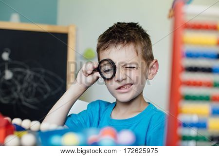 Toothless schoolboy looking through a magnifying glass