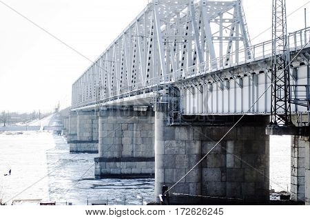Railway bridge over the frozen river in the winter on a cloudy day