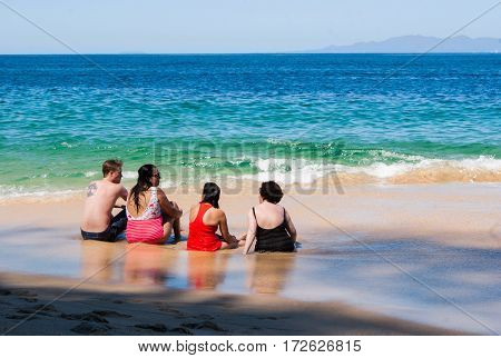 Two mature women and a young couple sitting on a beach