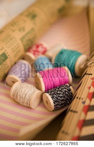 spools of colorful thread on holidays wrapping paper. Gift packing. Material for present package. Christmas birthday and celebration concept