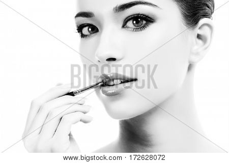 beautiful young woman applying lips makeup with cosmetic brush, white background, copyspace