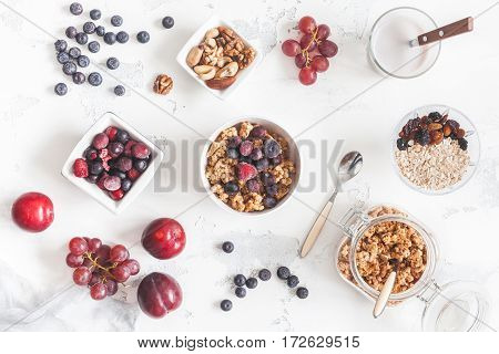 Breakfast with muesli fruits yogurt frozen berries nuts on white background. Healthy food concept. Flat lay top view