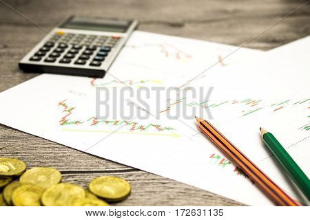 calculator, pencils and coins on graffica the Dow Jones on forex market at grey table