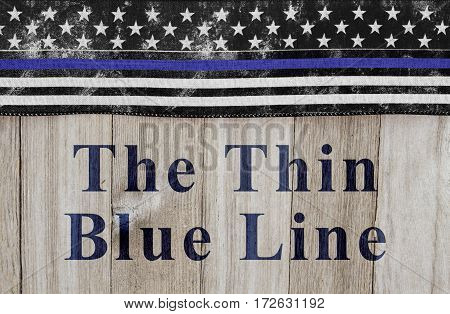 The thin blue line message USA thin blue line flag on a weathered wood background with text The Thin Blue Line